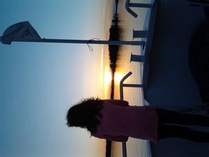 det här bilden togs på räkbåten Tor 17maj min dotter moa står i fören och blickar ut över mälaren vid solnedgången