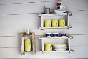 Vägghyllan består av gamla gamla ostformar – i dag rymmer de kaffe- och äggkoppar.