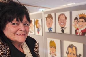 Helen Forslund framför några av sina karikatyrer hon målat genom årens lopp.