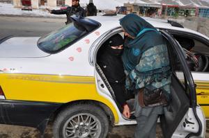 En kvinnlig polis undersöker en bil.
