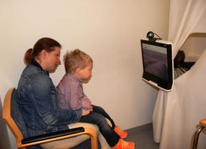 Axel Stengel Egrelius, tre år,  får sitta i mamma Åsas knä framför en skärm som visar olika filmer och bilder. En kamera registrerar hans ögonrörelser och avgör hur snabbt han kan uppfatta vad som är avvikande på bilden.