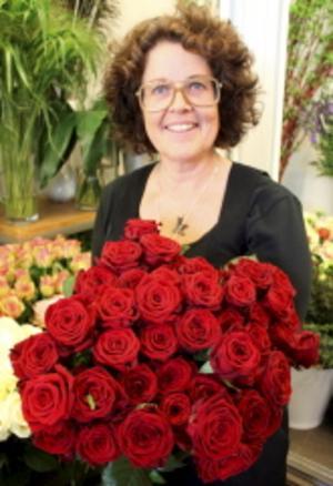 Karin Davidsson med röda rosor som är allra populärast när folk skall välja kistdekoration. Foto: Mikael Stenkvist