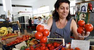 Giuseppina säljer grönsaker från Sicilien på den lokala marknaden.