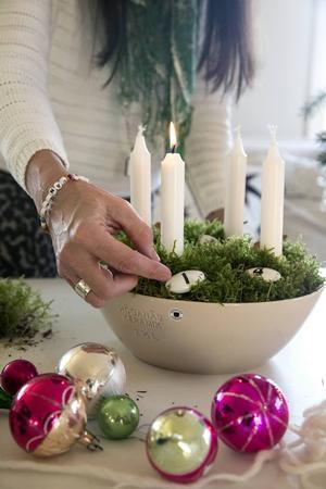 Grön mossa och vita ljus. Susanne dekorerar med siffror som egentligen är till för att sättas på kökslådor.