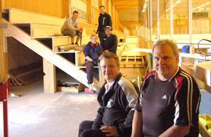 Älvdalens HC:s ordförande Lars Andersson och klubbens allt-i-allo Owe Strid gläder sig åt nya läktare i ishallen som klubben och kommunen finansierat tillsammans. I bakgrunden ses fyra av klubbens aktiva spelare, Johan Boberg, Andreas Olsson, Simon Persson och Fredrik Wallin, som för dagen är snickare och jobbar med den nya läktaren.