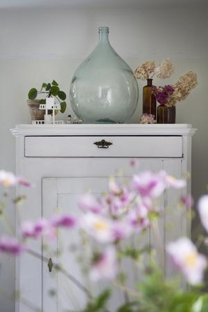 På det vita skåpet, tillverkat av snickaren som en gång bodde i huset, finns bland annat gamla flaskor som används som blomvaser.
