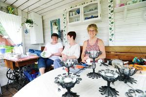 Ulla Jonsson, till vänster, målar porslin och Eva Hansson, till höger, gör luffarslöjd. I mitten Ulla Ringård, som den här dagen hade fullt upp med att servera fika.