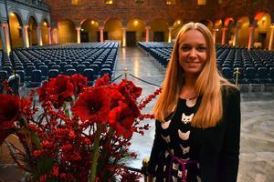 Här står Johanna bredvid blomblad stora som lampskärmar i hjärtat av Blå Hallen.