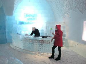 En drink i baren: Anne med vantar på och bartendern behåller skinnmössan. Mattan av snö, borden av is från Torneälv.