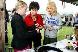 Elisabeth Bergqvist, mitten, lär och hjälper Maja Tegstad och Senya Ruuska att göra luffarslöjd.