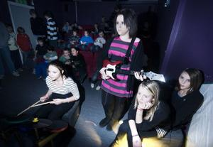 Moa Petersen trummar och Sanna Håberg plinkar på gitarren. Bredvid sitter Angelica Carlsson och Matilda Forslind.