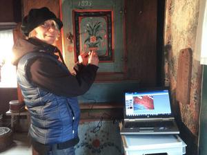 Anneli Nyström gör en mikroskopsundersökning av färgskiktet på ett sängskåp.
