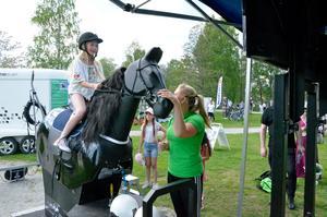 Den mekaniska hästen Monté Python lockade många barn.  Alice Toll var en av dem som provade på med hjälp av Hanna Eriksson från Fornaboda Travskola.