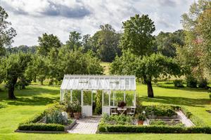 I trädgården finns ett växthus som dignar av tomater, gurkor och melon så här års. Intill finns pallkragar me grönsaker.