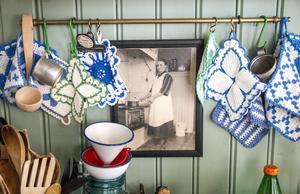 Färggranna grytlappar och ett fotografi på en kär släkting hänger över spisen.