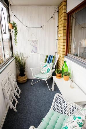 Balkongen på entréplanet har piffats till med en matta, ljusslingor, växter och luftiga möbler.