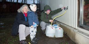 Kerstin Svensson, Joar-Rike Persson, Annica Persson fick hämta vatten på Rimbo brandstation. – Tre dunkar borde räcka. Vi är sparsamma med vattnet, säger Kerstin Svensson.