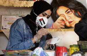 Den palestinska konstnären  Samah Saed dekorerar ansiktsmasker i Gazaremsan.  Foto: Adel Hana/PÅ
