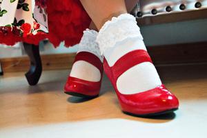 Blänkande röda lackskor och sockor med spets passar till fest.