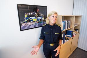 Fotografiet som hänger på väggen i Elisabeth Anestads arbetsrum är viktig för henne. Polisbilen översållad med blommor efter terrordådet på Drottninggatan i Stockholm väcker en rad känslor.