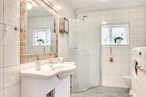 Det helkaklade badrummet är modernt inrett i ljusa färger. Foto: Johan Blomquist, Bostadsfotograferna