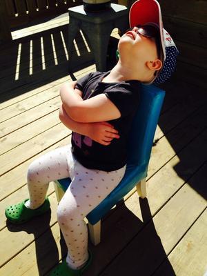 Agnes 2,5 år sitter på altan och lapar sol.