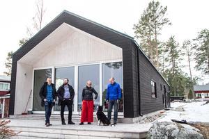 Husets  östra gavel vetter mot havet och Sörfjärdens sandstrand. Daniel Gunsth och Ola Wigg från Nordanstigs kommun uppvaktar Lena och Per Callermo.