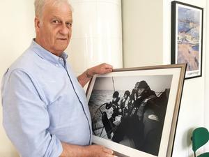"""Dennis Harding visar upp det inramade fotografiet på sig själv under en stormig seglats med sonen och dennes kompisar. """"Det var sista turen med gänget"""", säger han. Nu är det mer landbaserad träning som gäller."""