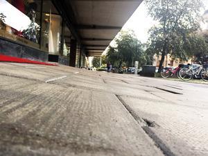Från marknivå syns det tydligt hur hela trottoaren har sjunkit ner. Här har människor med rörelsehinder svårt att ta sig fram.