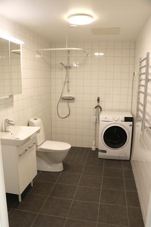 Nu. Nytt badrum med kakel och klinker samt en tvättmaskin.