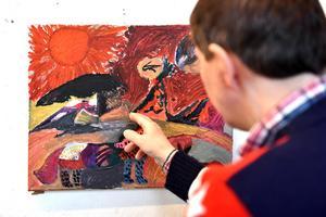 Daniel Persson visar upp konsten som nu sitter längs väggarna i Rosa huset.