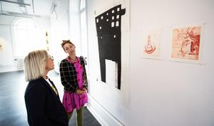 Linda Frisk och Sandra Berg Mozard diskuterar ett verk på utställningen.