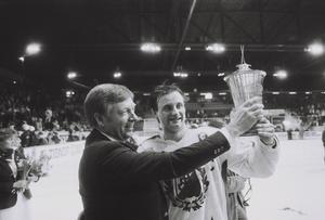 Två Södertäljesöner. Rickard Fagerlund, ordförande i Svenska ishockeyförbundet, ger pokalen till SSK:s lagkapten Anders Eldebrink.