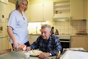Sune Eriksson i Edsbyn får besök av hemtjänsten fyra gånger per dag. Här hjälper Lena Johansson honom med lunchen. Även Lena konstaterar att arbetet har förändrats och blivit stressigare sedan hon började jobba.