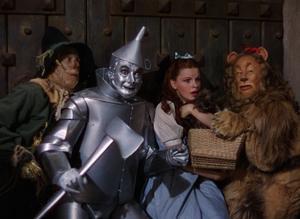 Fågelskrämman Hunk (Ray Bolger), plåtmannen Hickory (Jack Haley), Dorothy (Judy Garland) och lejonet Zeke (Bert Lahr) i