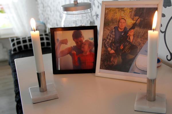 På ett litet bord i köket står fotografier och tända ljus. På ena fotot leker Simon med ett syskonbarn – på det andra är han ute och jagar med en av sina hundar.