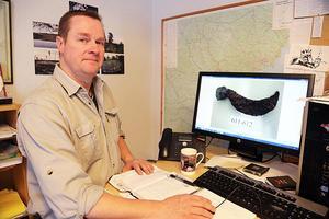 Ola George med bilder på en krumkniv hittad vid en av många utgrävningar.