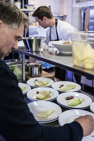 Den prisbelönta kocken Jonas Svensson förbereder huvudrätten som bestod av hjälmaregös med spetskål, fänkål, dill och jordärtskocka.