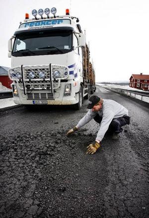 """Göran Lalander visar hur asfalten, som lades i höstas, förstörts vid Medstugan. """"Skalstugevägen är en långdragen katastrof"""", säger han."""