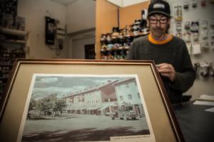 I förgrunden syns bilden av hur det såg ut på Västmannavägen på 60-talet, med bland annat Adenskogs Färg som en av butikerna.