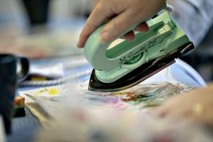 Man smälter vaxkritan på strykjärnet och för över färgen på papperet.