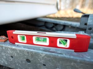 Med ett vattenpass kontrolleras att husvagnen står plan så att den inte rullar iväg.