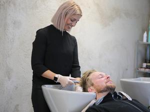 Annika Sundt trivs med att vara kreativ och jobba med människor. Här förbereder hon Fredrik Malmsten för en klippning.
