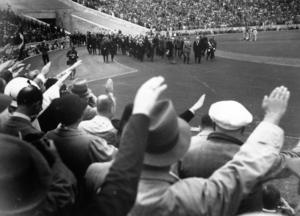 Olympiska spelen i Berlin 1936. Publiken hyllar Adolf Hitler när han marscherar in på arenan för att öppna spelen. Några år senare skulle andra världskriget inledas. Arkivfoto: TT