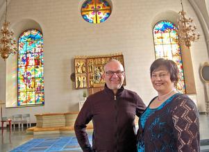 Arbetsgruppens Leif Sund och Åsa Hampgård inne i kyrkan, som domineras av altarskåpet och konstnären Anders Gabrielssons stora korfönster, som berättar bygdens historia