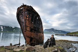 Eva Sigurbjörnsdóttir, som har drivit Hotel Djúpavík i 30 år, ses med hunden Freja vid det rostiga fartyget MS Sudurland.   Foto: Nicklas Elmrin
