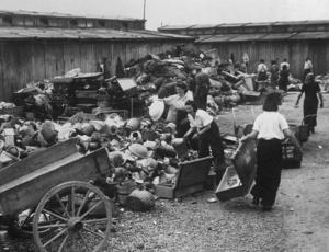 Bagage och ägodelar. Kvinnor sorterar fångarnas tillhörigheter som de tvingats lämna ifrån sig när de klev av godståget. Effekterna sorteras, oftast för vidarebefordran till Tyskland.