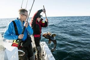 Ulf har fånat en torsk och för hjälp av Magnus att landa den i båten.