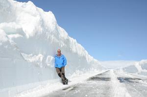 Bertil Forsmark lutar sig mot de fyra meter höga snövallarna längs Stekenjokkvägen. Vägen kommer dock inte att öppnas för allmänheten förrän om ett par veckor.