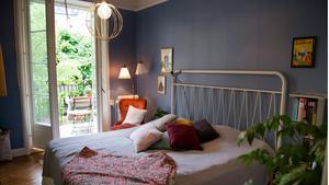Sovrummet är målat med Lindas favoritnyans av blått, och inredd med en blandning av gammalt och nytt. Dubbeldörrar leder ut till en av lägenhetens två balkonger - den ena byggdes efter att familjen flyttat in. Sänggaveln är nyproducerad, medan den röda Emmafåtöljen är vintage.